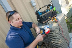 HVAC contractor servicing an air conditioner